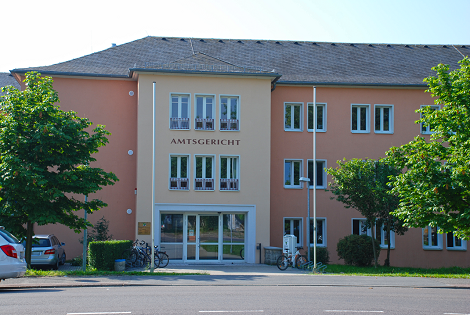 zweistöckiges Gebäude mit breitem Eingangsbereich, umgeben von Wiese und Bäumen